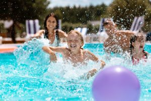 Ball,In,Pool.,Cheerful,Happy,Parents,And,Children,Laughing,While